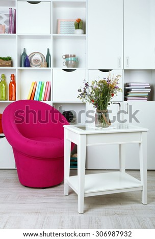 White living room with armchair and bookcase - stock photo