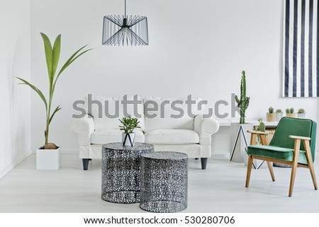 White living room with decorative openwork table and sofa