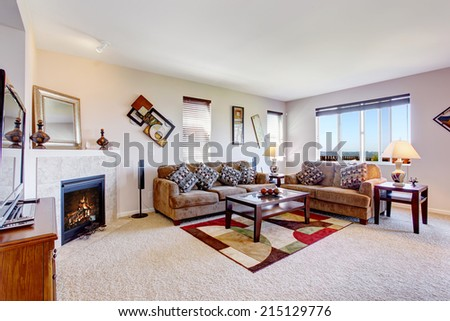 White living room with fireplace and colorful rug. Furnished with brown couches and coffee table - stock photo