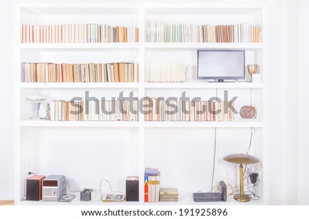 white living room with modern wooden white bookshelf and different books inside, domestic atmosphere, library background indoors, clean and modern decoration - stock photo