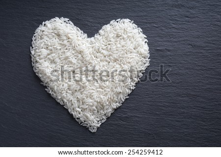 white long-grained rice in heart shape on black slate serving board                                - stock photo