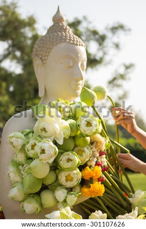 White lotus flower in hand of white Buddha image ; The lotus is one of the most well-known symbols of Buddhism. White Lotus this represents the state of spiritual perfection and total mental purity.  - stock photo