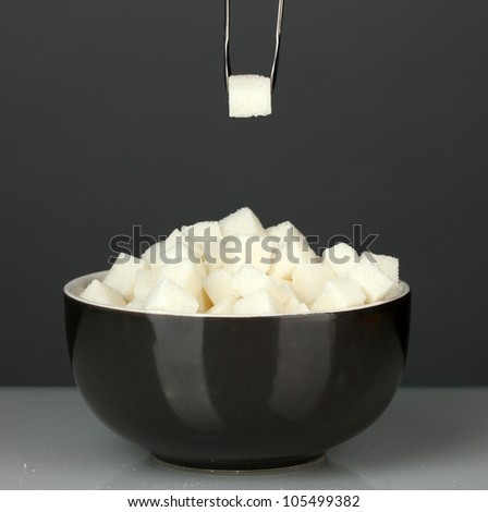 White lump sugar in bowl with sugar-tongs on grey background