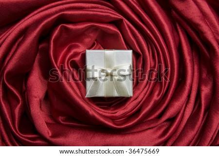 White luxury gift box on red satin - stock photo