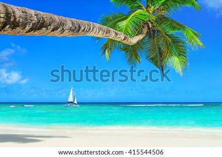 White luxury yacht under sail at ocean waves against azure tropical beach with white sand, transparent turquoise water and coconut palm tree in bright sunny day - vacation background - stock photo