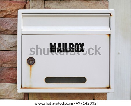 white mailbox mounted at stone wall
