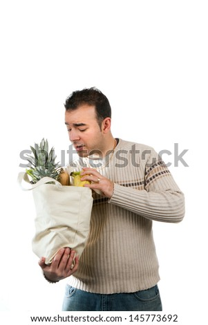 White male grocery shopper looking for an item in his grocery bag. - stock photo