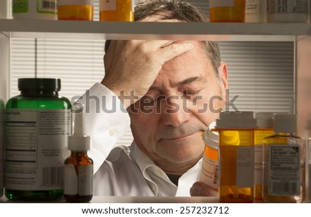 white male looking at assortment of prescription drugs - stock photo