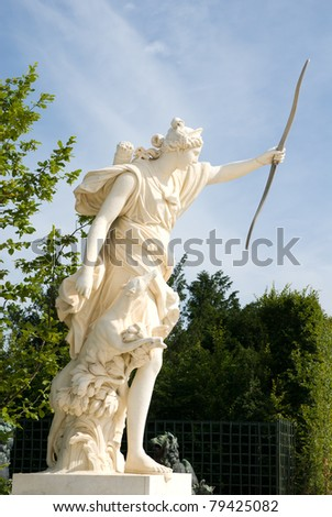 White marble Statue with hunter in the Versailles Palace garden,City Paris, France. The Palace Versilles is a royal chateau and it was added to the UNESCO list of World Heritage Sites in 1979. - stock photo