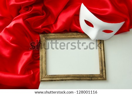 White mask, empty frame and red silk fabric, isolated on white - stock photo