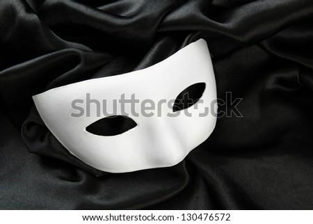 White mask, on black silk fabric - stock photo