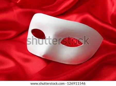 White mask, on red silk fabric - stock photo