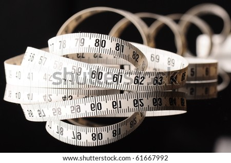 white measurement tape on black - stock photo