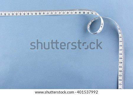 White measuring tape on a grey background - stock photo