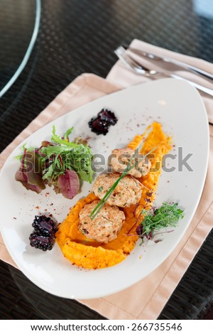 White meat patty cakes with pumpkin mash on restaurant table - stock photo