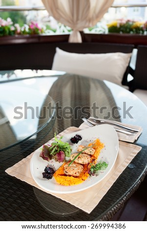 White meat patty cakes with pumpkin on restaurant table - stock photo