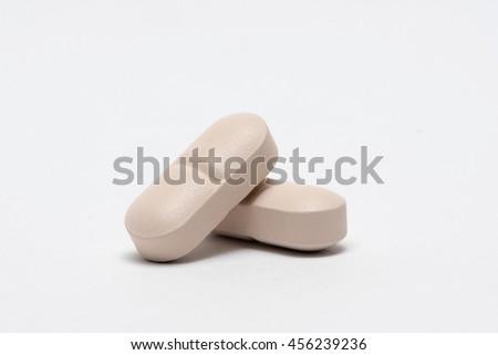 White medicine pills heap. Isolated on white background. - stock photo