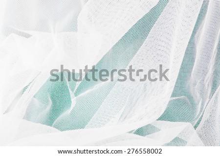 white mesh fabric on green background - stock photo