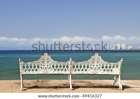 White metal bench on Malecon at Pacific ocean in Puerto Vallarta, Mexico - stock photo