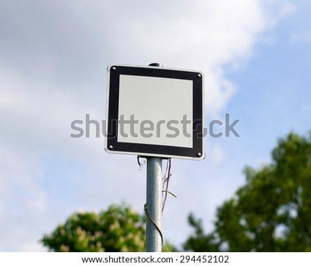 White metal sign with black frame bolted to a metal pole on the road