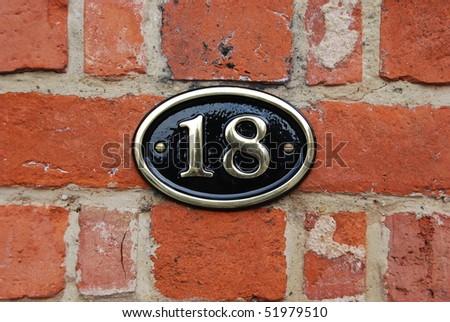 white metallic number (18) hanging a brick wall - stock photo