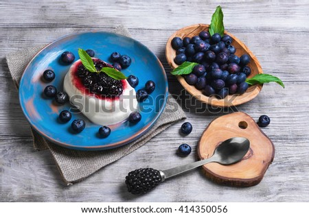 White milky creamy berry pudding with berries, blackberries, blueberries, spoon for pudding, worn blue ceramic dish, mint leaves on burlap, on a light wooden background surface rustic - stock photo