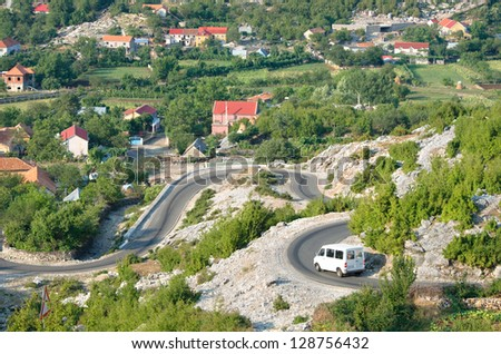 white minibus on the winding road from Razem to Shkoder, Albania - stock photo