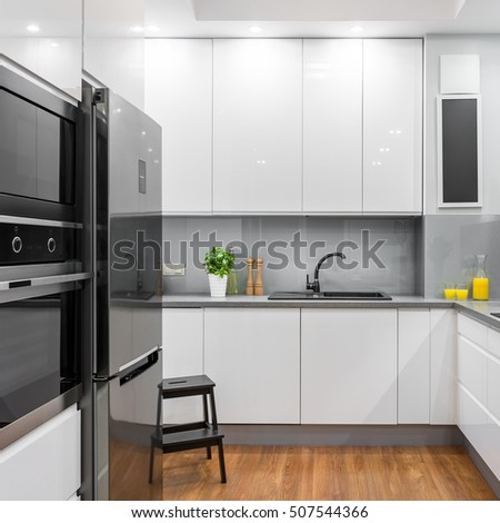 White modern kitchen with fridge, oven and microwave