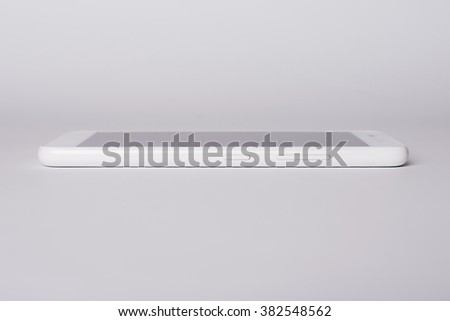 White modern smartphone with blank screen lies on the surface, isolated on white background. Elements. - stock photo