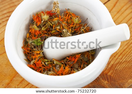 white mortar with dry marigold flower on wooden background - stock photo