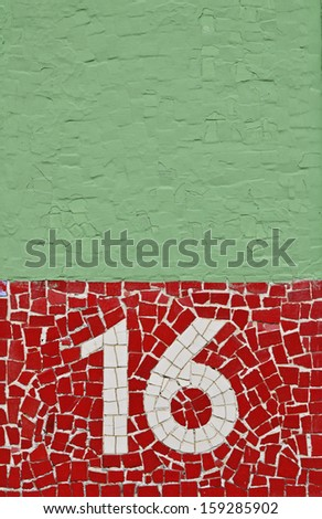 White Mosaic Number Sixteen 16 on Red Background with Green Brick Copy Space Above - stock photo