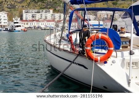 White motor boat with lifebuoy in marina of Balaklava city, Crimea. - stock photo