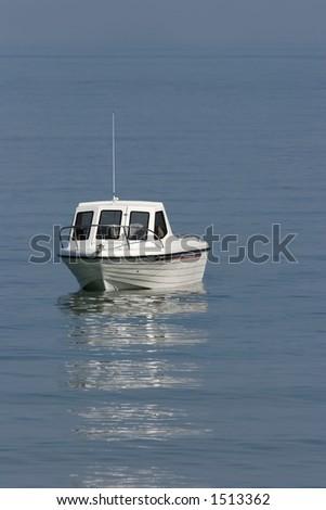 White motor cruiser on a calm blue sea. - stock photo