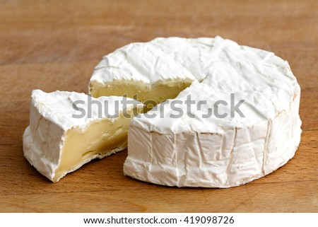 White mould cheese with cut slice isolated on wood.