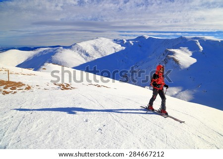 White mountain slope and ski mountaineer ascending in sunny winter day - stock photo