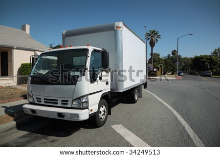 White moving truck on suburb street - stock photo