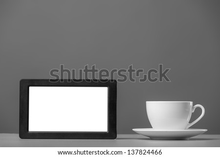 White mug and tablet computer on a gray background. - stock photo
