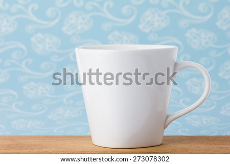 White mug cup on wooden board with blue background. - stock photo