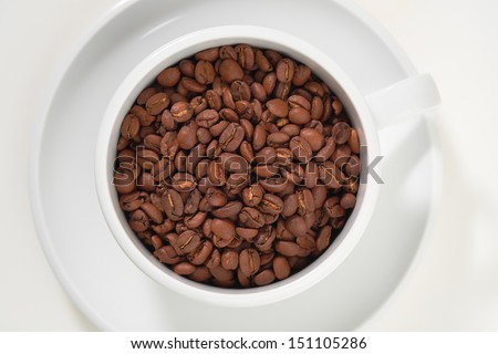 White mug with coffee beans in it on a white isolated background.