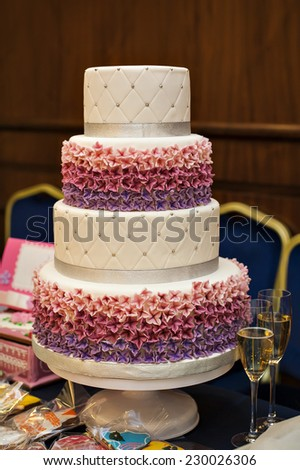 white multi level wedding cake with pink flower decorations. - stock photo