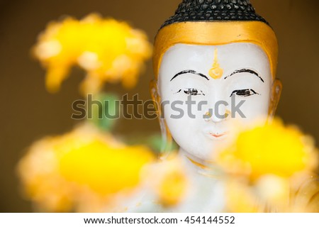 White Myanmar buddha statue with yellow flower - stock photo