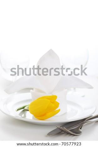 White napkin with tulip on white plate- Spring time - stock photo