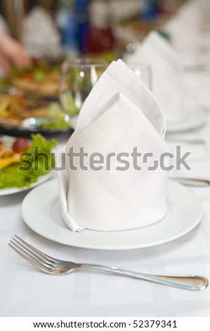 white napkins folded as triangles on plates, in perspective, on laid banquet table, shallow DOF