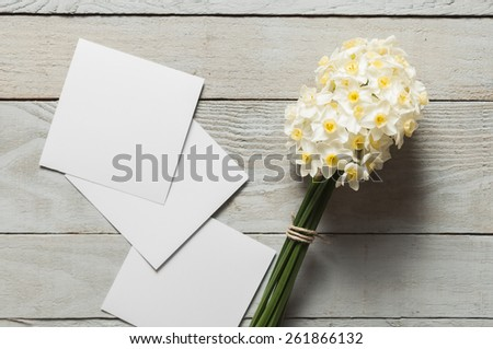 White narcissus flowers and blank paper pieces on wooden background - stock photo