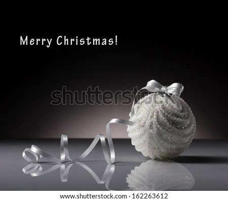 white new year's ball with white ribbon on dark grey-black background - stock photo