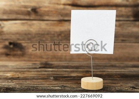 White note paper on a holder on brown wooden background - stock photo