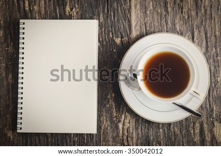 White notebook and cup of black tea on wooden table with vintage and vignette color