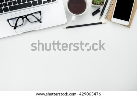 White Office Desk Table With Laptop, Cup Of Coffee And Supplies. Top View  With