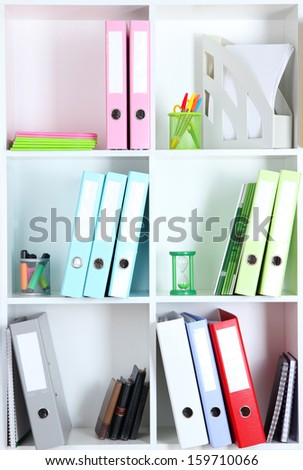 White office shelves with folders and different stationery, close up - stock photo