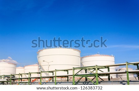 White oil reservoir. Oil and gas refinery plant. Industrial scene of oil field. Oil industry and blue sky - stock photo